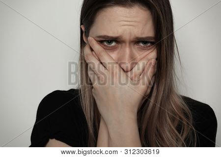 Scared Woman Covering Mouth With Her Hands On Light Background. Stop Violence