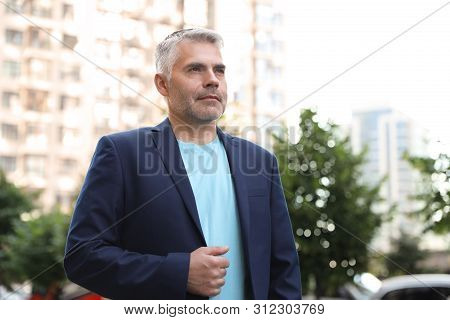 Portrait Of Handsome Mature Man In City Center. Space For Text