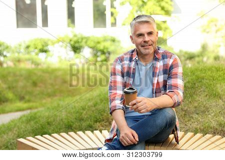 Handsome Mature Man With Coffee On Bench In Park. Space For Text