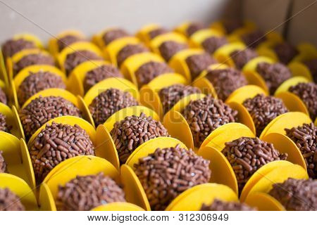Many Chocolate Candy Balls With Chocolate Sprinkles In A Box