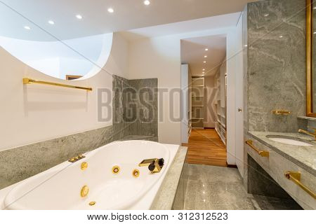 Luxury bathroom with large hydromassage, green marble and gold sinks. Nobody inside