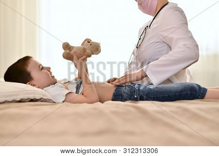 Doctor On Call At Home Of A Child Who Has A Stomach Ache. A Contented Boy Is Lying On The Bed Holdin