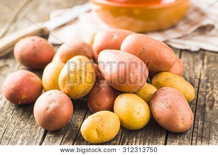 Fresh potatoes. Raw potatoes on old wooden table.