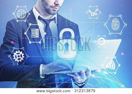 Businessman Using Laptop With Double Exposure Of Earth Hologram And Cyber Security Icons. Concept Of