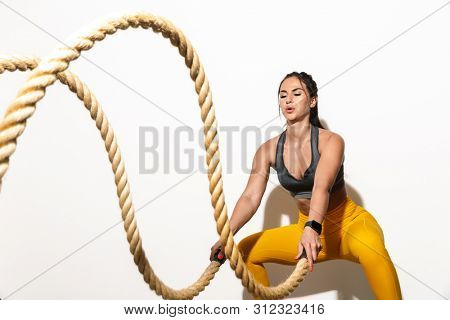 Photo of strong concentrated amazing young sports fitness woman isolated over white wall background make exercises with ropes.