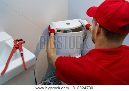 Plumbing Services - Plumber Working In Bathroom Installing Toilet Wc Water Tank