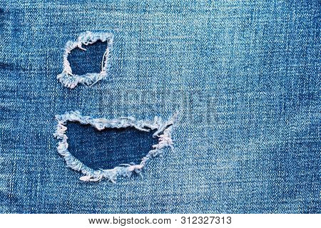 Hole On Denim Jeans. Ripped Destroyed Torn Blue Jeans Background. Close-up Blue Denim  Jean Texture