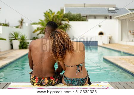 Rear view of young African-american couple sitting together near swimming pool at the backyard of home. Summer fun at home by the swimming pool