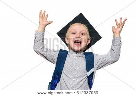 Portrait Of A Joyful Blond Boy With Academic Hat And A School Bag. Hands Up. Isolate