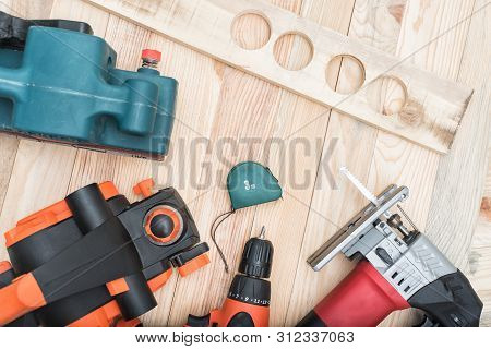 Set Of Handheld Woodworking Power Tools For Woodworking And Workpiece Lies On A Light Wooden Backgro