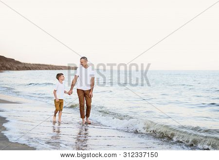 Father And Son Go By The Hand Along The Sea Coast. Family Vacation. Friendship