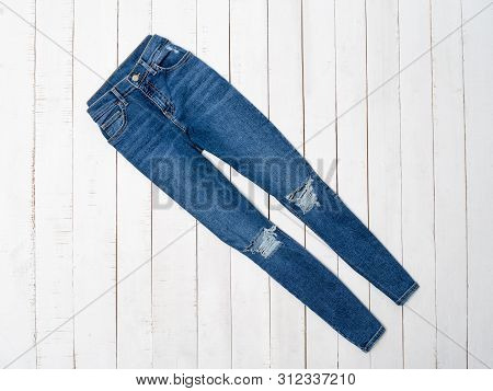 Blue Ragged Jeans On A White Wooden Background. Clothing Concept. Flat Lay