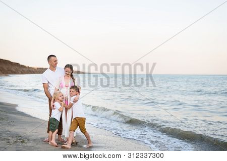 Happy Family Of Four Hugging On The Sea Coast. Parents, Pregnant Mother And Two Sons.