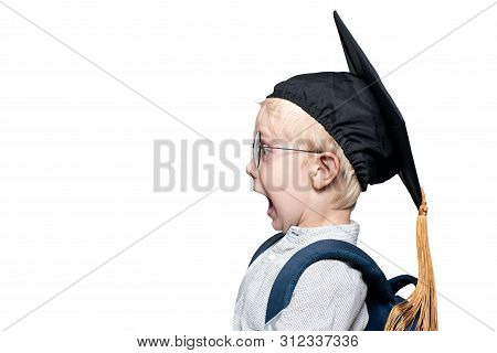 Portrait Of A Surprised Blond Boy In Glasses, An Academic Hat And A Schoolbag. School Concept. Isola