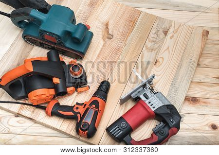 Set Of Handheld Woodworking Power Tools For Woodworking On Light Wooden Background. Close Up.