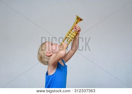 Little Cute Blond Boy Playing Trumpet On Light Background.
