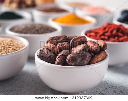 Raw Cocoa Bean In Small White Bowl And Other Superfoods On Background. Selective Focus. Different Su