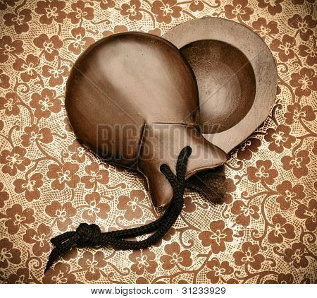 a pair of spanish castanets arranged like a heart on a patterned background