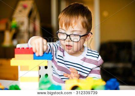 Boy With Down Syndrome At Home Playing With Colored Blocks