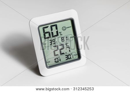 Humitidy And Temperature Reading Device, Closeup On A White Wooden Table