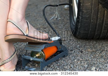 Woman inflating car tyre by mechanical foot air pump. She does it herself. Feets in sandals on the side of the road. Close-up view. Old worn wheel tyre in the frame. poster