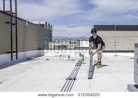 Electrician Lifting Up A Bundle Of Conduit On A Roof Top.
