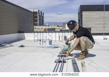 Electrician Running Wire Through Conduit On A Building Roof Top.