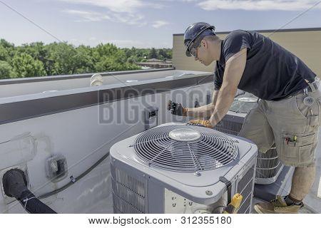Hvac Technician Pulling A Breaker On A Condenser.,