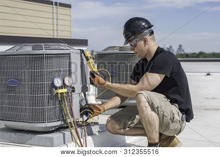 Hvac Technician Wearing Safety Gear Inspecting An Air Conditioner