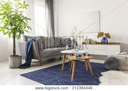 Flowers On Wooden Coffee Table In Fashionable Living Room Interior With Scandinavian Design