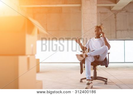 young casual african american businessman using a mobile phone while taking a break on construction site with sunlight through the windows during moving in at new startup office