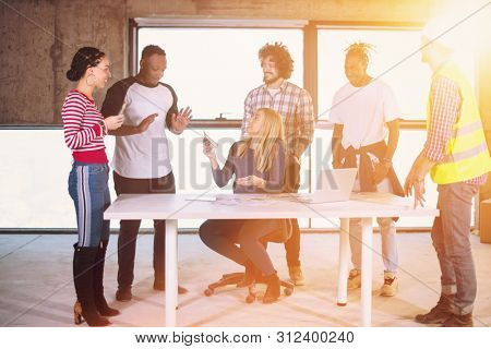 female menager giving money bonus for a well done job to her happy multiethnic business team with sunlight through the windows during movin in at new unfinished startup office building