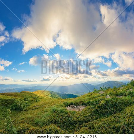Amazing Summer Landscape At Sunset. Fluffy Clouds In Golden Light Above The Mountain Ridge. Grassy M