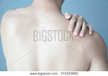 Closeup Man Hand Holding Shoulder With Pain On Blue Background, Health Care And Medical Concept
