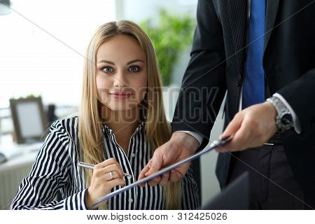 Beautiful Smiling Clerk Looking In Camera While Signing Important Document Clipped To Pad Portrait