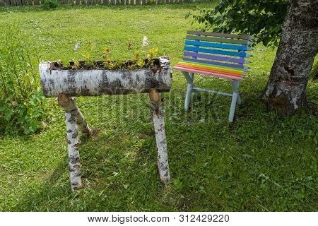 A Small Flower Garden Made Of Birch Logs And A Small Multi-colored Bench.