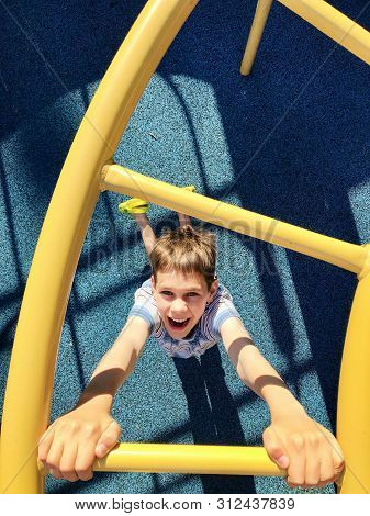 Boy Having Fun On A Monkey Bars. Young Boy Hanging On The Yellow Bars By His Hands.  Top View