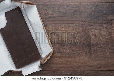 Top View Of Unwrapped Dark Chocolate Bar. Flat Lay Image Of Bitten Dark Chocolate On Brown Table. Ph