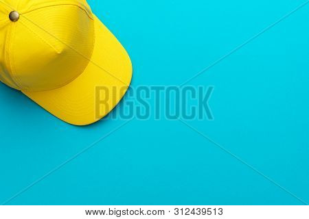 Top View Of Yellow Baseball Cap Over The Blue Torquoise Background. Flat Lay Mock-up Image Of Unisex