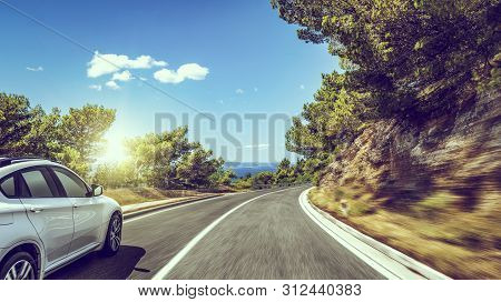 White Car Rushes Along The Road To The Sea.