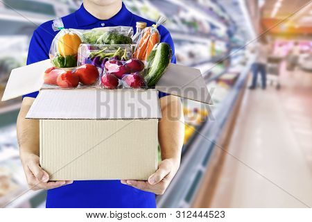 Food Delivery Service For Order Online Grocery Shopping Concept. Delivery Man In Blue Uniform Hand H