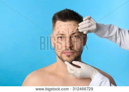 Doctor Examining Man's Face Before Plastic Surgery Operation On Blue Background