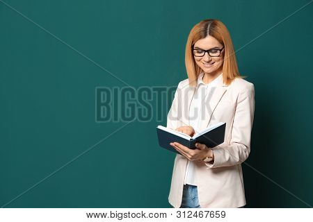 Portrait Of Beautiful Teacher With Book Near Chalkboard, Space For Text