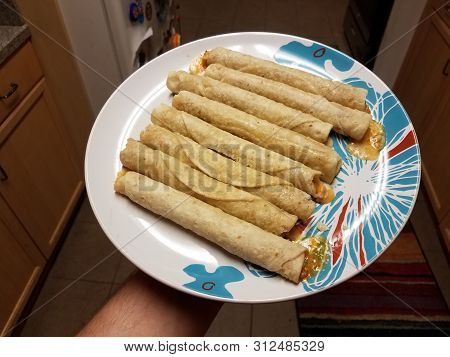 Hand Holding Taquitos On Plate In Kitchen