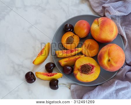 Closeup Of Plate With Peaches, Apricots And Cherries On Light Marble Background. Flat Lay, Top View.
