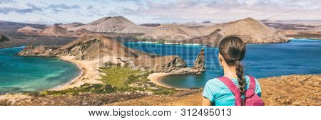 Galapagos islands cruise vacation tourist woman panoramic banner. Bartolome or Bartholomew island view on hiking shore excursion travel tourism. Hiker traveling in Ecuador.
