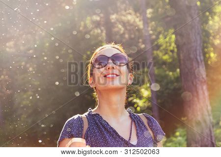 Beautiful Woman Smiling In Nature. Happy People Lifestyle. Woman Smiling In Sunshine With Water Drop