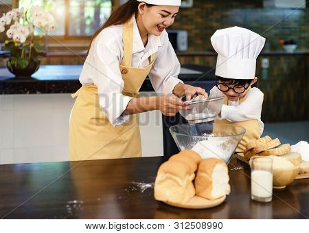 Happy Asian Family In The Kitchen.mother And Son Help To Make Cake.mom Teaching Boy Cooking Bread Do