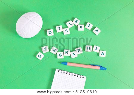 Dyslexia And Dysgraphia Words With An Open Notebook And Pen On Green Background, Reading And Writing