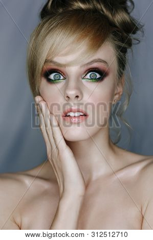 Shocked Emotoional Young Fashion Make-up Woman. Stunned, Fascinated Glamour Girl with Opened Mouth Big Eyes and Holding Hand near Face. Surpise, Wonder and Astonishment Concept. Vertical Photo poster